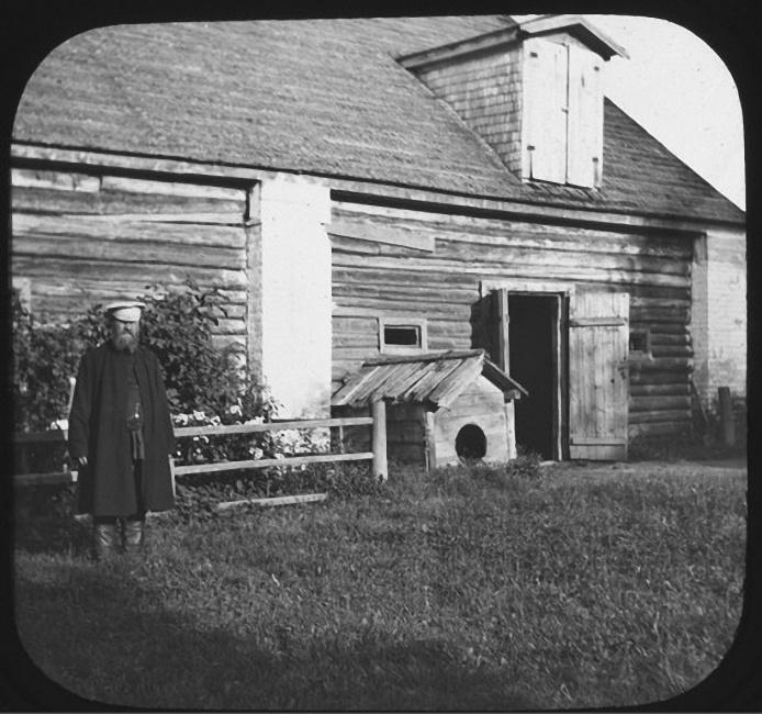 Слуга Иван стоит слева от бокового входа в амбар. Рядом со входом — собачья будка. Лето 1903 года