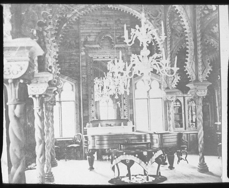 Интерьер комнаты в доме Ячевских. Изысканные деревянные колонны, куполообразные потолки сложной конструкции, встроенный книжный шкаф в дальнем углу комнаты. Стол со скатертью в центре комнаты и рояль. Люстра со свечами висит над столом. Лето 1903 года