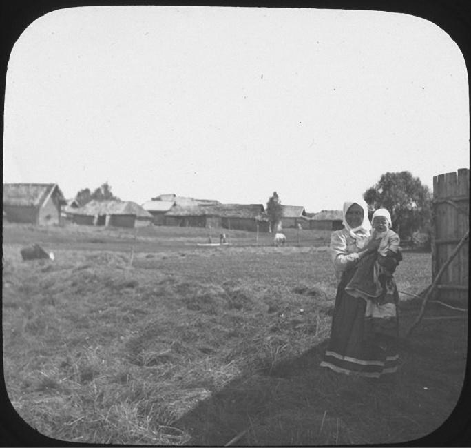 Женщина стоит в тени на правой части фотографии с ребенком на руках. На заднем плане деревня Рыльково. Лошади на выгоне в поле позади нее. Лето 1903 года